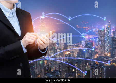 Asian business woman use smartphone technology in Smart city with communication network and big data system. - Stock Photo
