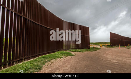 A portion of the steel border fence with a gate, Brownsville Texas, USA - Stock Photo