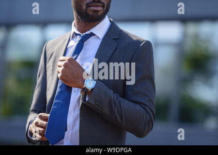cropped view of african american businessman touching tie while standing on street - Stock Photo