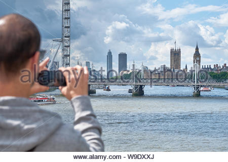 London, UK. 5th August, 2017. A man in the foreground takes a picture from a bridge looking across the river Thames towards Westminster. - Stock Photo