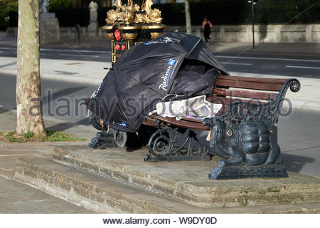 London, UK. 13th October, 2018. A homeless persons temporary shelter on an Embankment bench. - Stock Photo