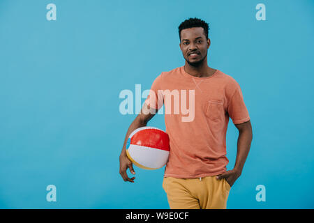happy african american man standing with hand in pocket and holding beach ball isolated on blue - Stock Photo