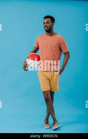 happy african american man standing with hand in pocket and holding beach ball on blue - Stock Photo