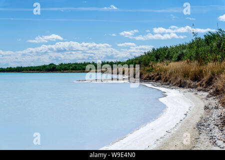 shore of a salty lake with a crust of salt along the coastline - Stock Photo