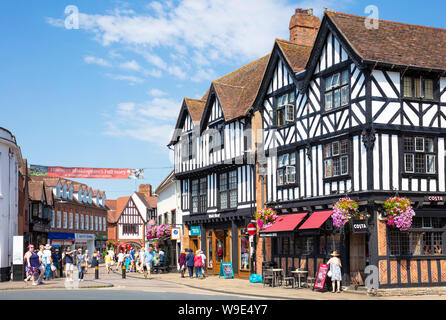 Busy central Stratford upon Avon town centre streets with half timbered buildings and flower baskets Warwickshire England UK GB Europe - Stock Photo