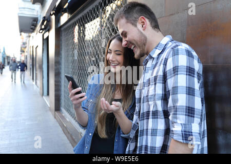 Happy couple checking surprising smart phone content standing in the street - Stock Photo