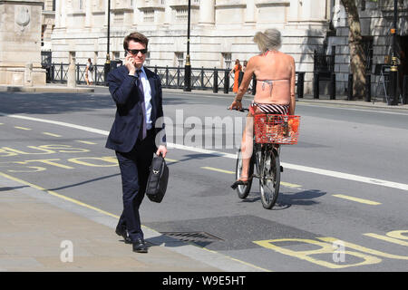 Westminster, London, UK, 13th Aug 2019. A sun worshipper in a bikini, and not much else, cycles down Whitehall in Westminster. Following days of rain and cooler temperatures, the warm weather marks a welcome change for Londoners. Credit: Imageplotter/Alamy Live News - Stock Photo