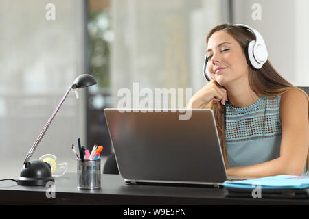 Happy girl listening to music wearing headphones in a room - Stock Photo