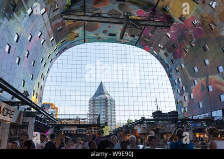 Rotterdam, Holland - July 30, 2019: Artwork at the wall of the Markthal and a view to the pencil building through the glass windows - Stock Photo