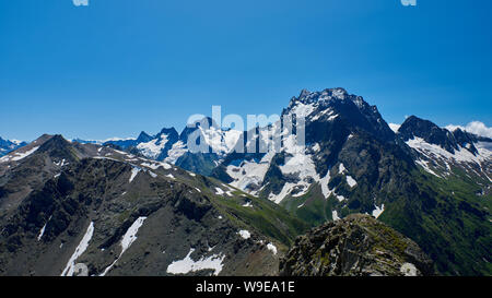 The black mountain peak in the foreground is a rocky ridge. North Caucasus, Russia - Stock Photo