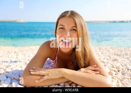 Excited young woman lying on pebbles beach. Close up portrait of happy girl on her summer holidays. - Stock Photo