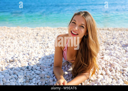 Excited young woman lying on pebbles beach. Close up portrait of happy girl on her summer holidays. Copy space. - Stock Photo
