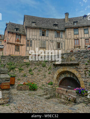 Conques, Midi Pyrenees, France - July 31, 2017: Small stone fountain in the square of the Cathedral of Conques - Stock Photo