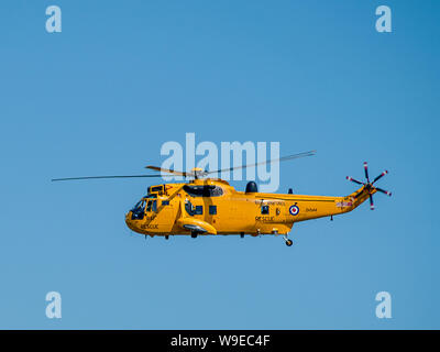 Yellow RAF rescue helicopter viewed from above Knab Rock in Swansea Bay during Swansea Air Show 2009. Swansea, Wales, UK. - Stock Photo