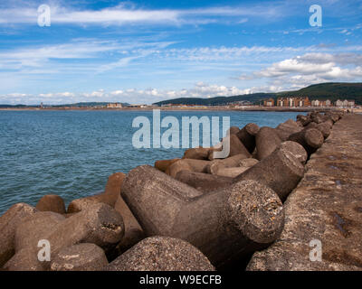 A view from the breakwater looking back to Aberavon Beach. Tetrrapod sea defences can be seen in the foreground. Aberavon, Wales, UK. - Stock Photo