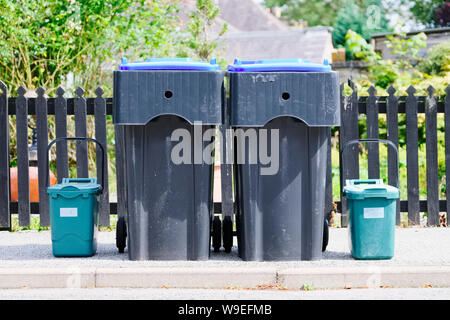 Green food bins and black wheelie bins in tidy row outside house and garden fence - Stock Photo