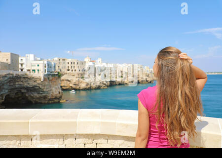 Summer holidays in Apulia. Back view of beautiful young woman enjoying Polignano a mare view, Mediterranean Sea, Italy. - Stock Photo