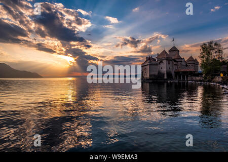 Chillon Castle on the shores of Lake Geneva at dramatic sunset - Stock Photo