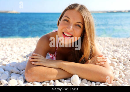 Pretty girl lying on pebbles beach. Summer holidays vacation on the beach concept. - Stock Photo
