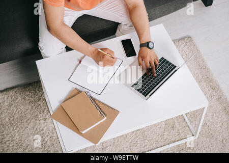 cropped view of young man using laptop and writing in notebook while sitting on sofa near desk - Stock Photo