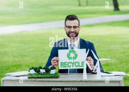 young businessman at table with windmills and sun batteries layouts holding card with recycle inscription