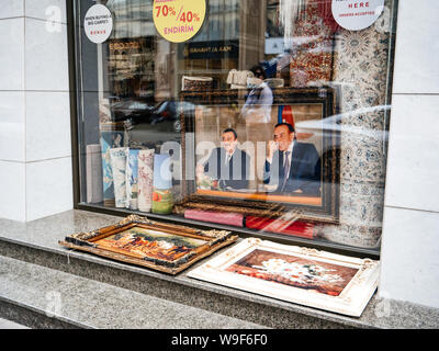 Baku, Azerbaijan - May 2, 2019: Sale discount signs in the tourist shop - buy carpets, Heydar Aliyev portraits and flower paintings - Stock Photo