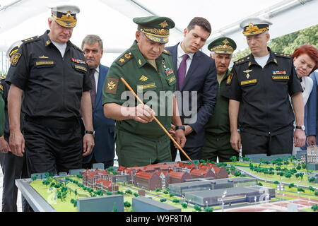 Russia. 13th Aug, 2019. KALININGRAD, RUSSIA - AUGUST 13, 2019: The Commander-in-Chief of the Russian Navy Admiral Nikolai Yevmenov (L), Russia's Minister of Defence Sergei Shoigu (C front), the Governor of the Kaliningrad Region Anton Alikhanov (C midground), and the Commander-in-Chief of the Russian Navy Baltic Fleet Admiral Alexander Nosatov (R front) look at a scale model of the Kaliningrad branch of St Petersburg's Nakhimov Naval School, which is to be built at Artilleriyskaya Street. Credit: ITAR-TASS News Agency/Alamy Live News - Stock Photo