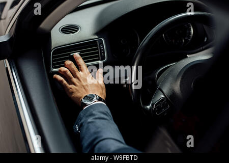 cropped view of african american businessman in suit touching air conditioning near steering wheel in car - Stock Photo