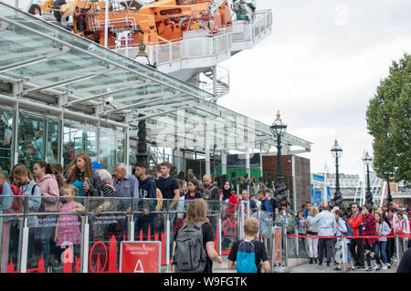 Thousands of tourists wait everyday in the queue at London Eye attraction to get onboard the iconic view of London and River Thames - Stock Photo