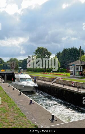 A private leisure river cruiser passing through Shepperton lock on a summers day, Surrey England UK - Stock Photo