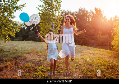 Happy little girl running with mother and holding baloons in hand. Family having fun in summer park at sunset. International Childrens Day Stock Photo