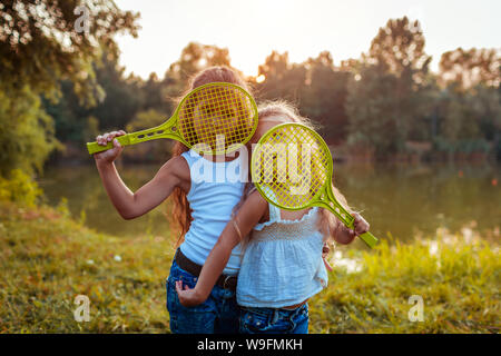 Little girls having fun outdoors after playing badminton. Sisters cover faces with rackets in summer park. Kids. International Childrens Day