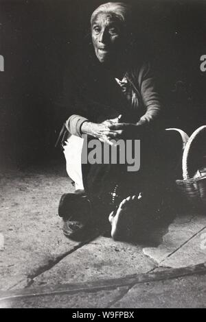 Fine black and white art photography from the 1970s  of a woman street peddler trying to make the best of her situation - Stock Photo