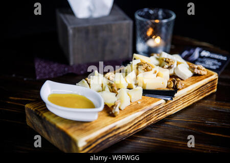 Cheese platter with different cheeses, nuts. styled cheese variety selection on wood board. - Stock Photo