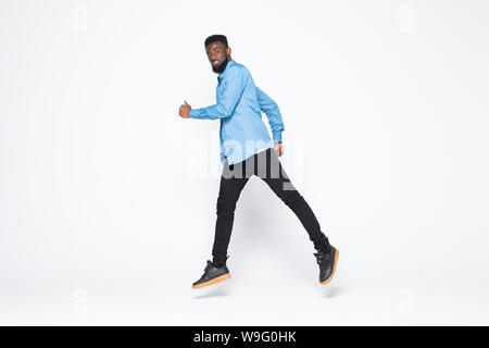Funny creative black man in fantasy having fun one on white background jump, dance, running to dream, copy space for logo or advertising, African Amer - Stock Photo