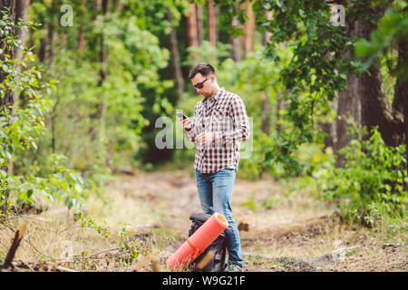 Hipster young man with backpack using smart phone on beautiful nature.Travel concept. Outdoor travel. Travel and explore. Backpacker male Going in - Stock Photo