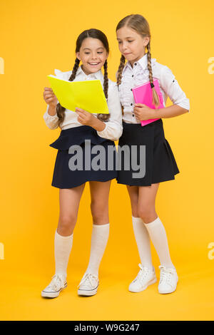 Knowledge day. School day. Kids cute students. Schoolgirls best friends excellent pupils. Schoolgirls wear school uniform. School friendship. Girl with copy books or workbooks. Study together. - Stock Photo