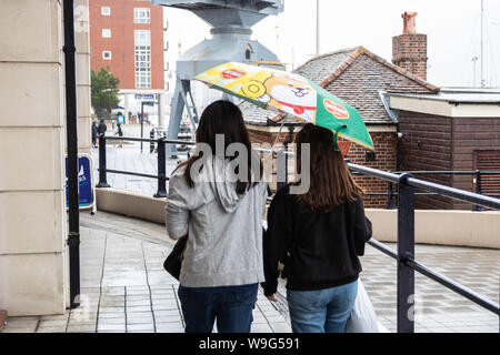 Two women taking shelter from the rain under one umbrella