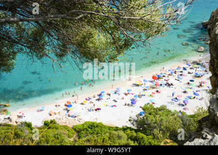 (Selective focus) View from above, blurred beach full of beach umbrellas and people sunbathing and swimming on a turquoise water. Cala Gonone, Italy. - Stock Photo