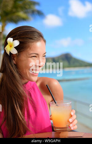 Beach bar party drinking friends toasting Hawaiian sunset cocktails having fun. Asian woman looking at camera holding alcoholic drink cheering in Waikiki beach, Honolulu city, Oahu, Hawaii USA. - Stock Photo