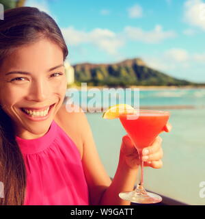 Woman drinking cocktail alcohol drinks at beach bar resort in Waikiki, Honolulu city, Oahu, Hawaii, USA. Asian girl tourist looking at camera toasting a glass of Hawaiian drink at sunset. - Stock Photo