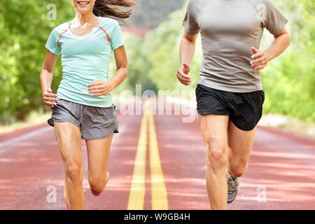 Young couple running on road. - Stock Photo