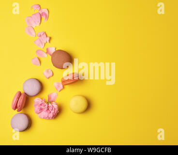 multi-colored macarons with cream and a pink rose bud with scattered petals on a yellow  background, top view, flat lay, copy space - Stock Photo