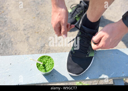 Green smoothie and running - healthy lifestyle. Closeup of male runner's sport shoe tying laces on park bench for diet and weight loss concept for men. Getting ready for jogging and cardio workout. - Stock Photo