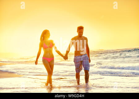 Young couple in swimwear walking at beach. Multiethnic romantic woman and man partners are holding hands while enjoying summer vacation. Loving tourists are enjoying sunset at beach. - Stock Photo