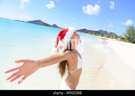 Christmas Santa hat bikini woman on beach vacation holiday getaway. Girl free and happy with arms outstretched of joy on tropical Caribbean beach. Beautiful girl in bikini having fun under the sun. - Stock Photo