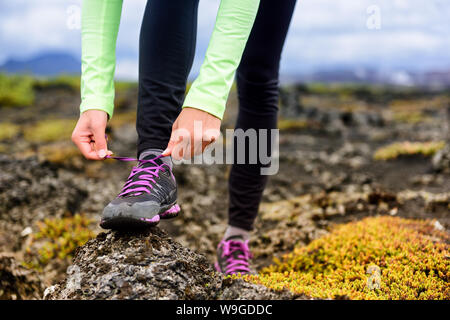 Trail runner woman getting ready to run on rocky mountain mud race in autumn. Athlete tying up laces of running shoes. Closeup of hands. - Stock Photo