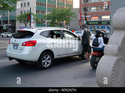 Montreal, Quebec Canada. Jul 2019. A homeless man earning some money by cleaning a cars windshield at an intersection. - Stock Photo