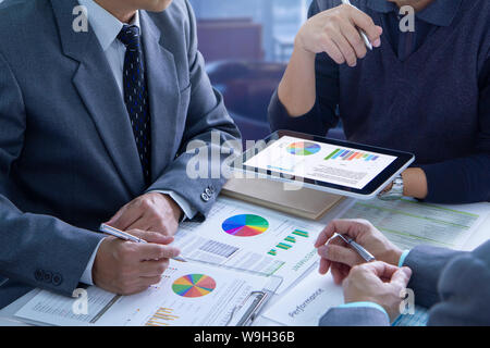 Businessmen are deeply reviewing financial reports for a return on investment or investment risk analysis and business performance.