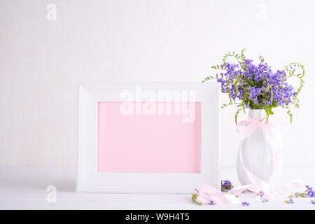 White picture frame with lovely purple flower in vase on white wooden table. - Stock Photo